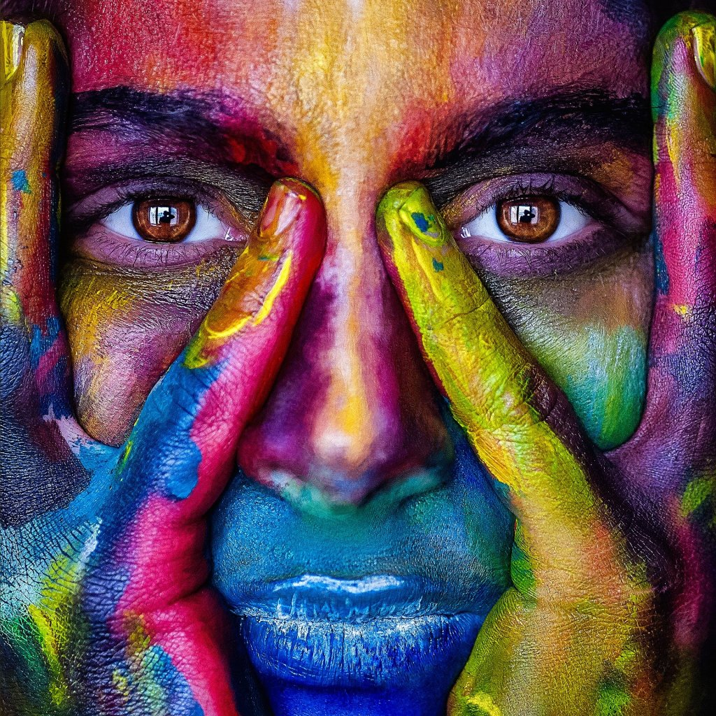 Woman covered in multi-coloured paint staring at the camera, hands against her cheeks.